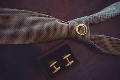 Laço do casamento, alianças de casamento do ouro e botão de punho, cor acolhedor escura Fotografia de Stock Royalty Free