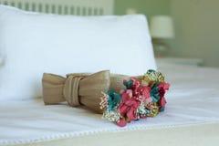 Laço do casamento sobre uma cama branca fotos de stock royalty free