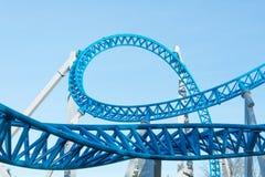 Laço e para girar sobre uma montanha russa azul em um parque de diversões foto de stock royalty free