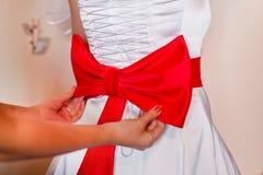 Laço vermelho no vestido da noiva Imagens de Stock Royalty Free