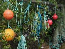 Laços azuis da corda, flutuadores vermelhos e alaranjados e rede de pesca que pendura entre o arbusto no suporte de madeira imagens de stock royalty free
