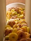Laços do cereal que derramam fora de uma caixa Fotografia de Stock Royalty Free