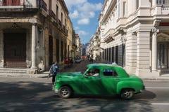 从La哈瓦那中心,与绿色老汽车的牛奶店古巴生活的街道视图 库存图片