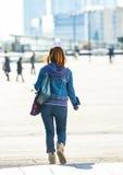 La防御,法国2014年4月10日:走在企业centrer街道上的后面观点的一名深色的妇女  她穿蓝色牛仔裤和 库存照片