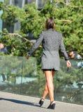 La防御,法国2014年4月10日:走在街道上的女商人的画象 她看非常偶然,穿着短裙, hig 库存照片