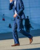 La防御,法国2014年4月09日:走在街道的商人侧视图 他佩带一非常典雅的蓝色衣服和高quali 图库摄影