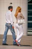 La防御,法国- 2006年8月30日:走在街道的时髦的夫妇 人佩带蓝色牛仔裤的和妇女白色气喘 图库摄影