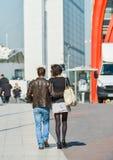 La防御,法国2014年4月10日:走在街道的时髦的夫妇 人穿着蓝色牛仔裤的和妇女短小灰色sk 免版税库存照片