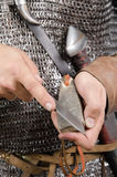 La 2ème moitié de guerrier normand du 11ème siècle affile le couteau Photo libre de droits