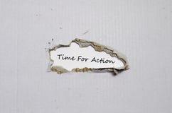 La época de palabra para la acción que aparece detrás del papel rasgado Imagenes de archivo