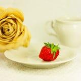 la Aún-vida con el juego de té, seca color de rosa y la fresa Fotos de archivo libres de regalías