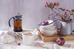 La Aún-vida con un espino, una taza de té y una caldera en un fondo de madera blanco Imagen de archivo libre de regalías