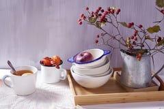 La Aún-vida con un espino, una taza de té y una caldera en un fondo de madera blanco Imagen de archivo