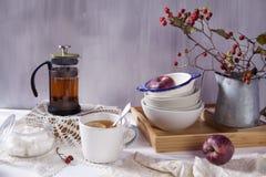 La Aún-vida con un espino, una taza de té y una caldera en un fondo de madera blanco Fotografía de archivo