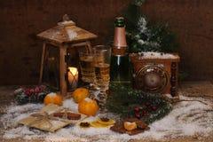 La aún-vida del Año Nuevo con champán, las mandarinas y el chocolate Imágenes de archivo libres de regalías