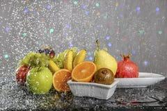 La aún-vida festiva de las frutas coloridas frescas en descensos y salpica del agua que cae Imagen de archivo libre de regalías