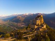 La abadía medieval vieja de la visión aérea se encaramó en el top de la montaña, montañas nevosas del fondo en la salida del sol  Fotos de archivo