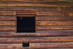 La abertura de la ventana en una pared de madera Fotos de archivo