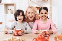 La abuela alegre abraza a los nietos felices que beben té en cocina foto de archivo libre de regalías