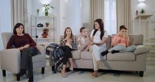 La abuela con sus nietos y la hija que mira una buena pel?cula en la TV tienen caras sonrientes y goce almacen de metraje de vídeo