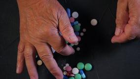 La abuela cuenta las tabletas multicoloras en la tabla negra en casa concepto de edad avanzada, medicación, tratamiento Primer de almacen de video