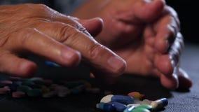 La abuela cuenta las tabletas multicoloras en la tabla negra en casa El concepto de edad avanzada, medicación, tratamiento Primer almacen de metraje de vídeo
