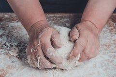 La abuela de una mujer mayor está amasando una pasta para cocinar el pan fotos de archivo