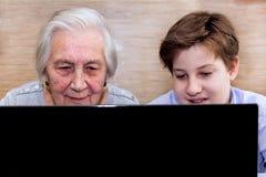 La abuela del nieto enseña a conocimiento de informática Imagen de archivo libre de regalías