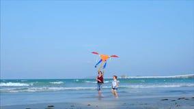 La abuela feliz con el niño la cometa que vuela que juega, la familia corre en la arena de un océano tropical que juega con almacen de metraje de vídeo