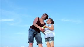 La abuela feliz con el ni?o la cometa que vuela que juega, la familia corre en la arena de un oc?ano tropical que juega con almacen de metraje de vídeo