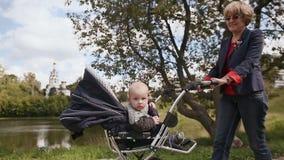 La abuela feliz joven camina con mi pequeño nieto, sentándose en una silla de ruedas En el fondo, un prado y una iglesia metrajes