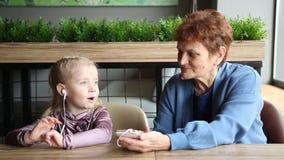 La abuela llevó los auriculares a su nieta para escuchar el cuento audio almacen de metraje de vídeo