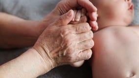 La abuela lleva a cabo las manos de su nieto querido almacen de video