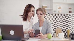 La abuela mayor está aprendiendo el pago en línea para hacer compras con smartphone almacen de metraje de vídeo