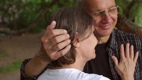 La abuela y el abuelo abrazan suavemente en parque almacen de metraje de vídeo