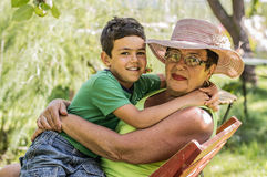La abuela y el nieto se están sentando en el jardín del verano Imagen de archivo