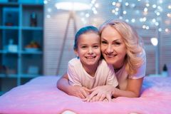 La abuela y la nieta están abrazando en la noche en casa fotos de archivo