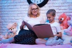 La abuela y la nieta están leyendo cuentos de hadas reservan en la noche en casa Fotografía de archivo