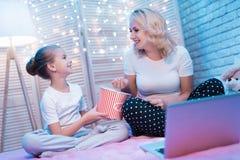 La abuela y la nieta están mirando película con palomitas en la noche en casa Imagenes de archivo