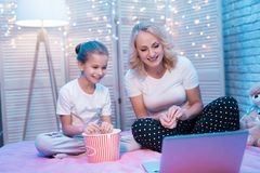 La abuela y la nieta están mirando película con palomitas en la noche en casa Fotografía de archivo libre de regalías