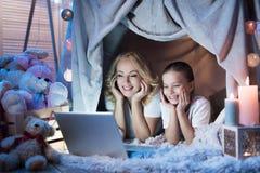 La abuela y la nieta están mirando película en el ordenador portátil en la casa combinada en la noche en casa Fotografía de archivo