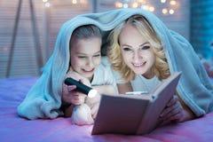 La abuela y la nieta son libro de lectura con la linterna debajo de manta en la noche en casa Fotos de archivo libres de regalías