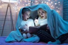 La abuela y la nieta son libro de lectura con la linterna debajo de manta en la noche en casa Fotografía de archivo libre de regalías