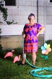 La abuelita gruñona tiene aversión los labores de jardinería Foto de archivo