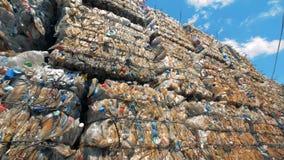 La abundancia apiló bloques de la basura con plástico alista para más lejos reciclar metrajes