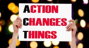 La acción cambia cosas manos femeninas que llevan a cabo un cartel Fotografía de archivo libre de regalías
