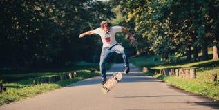 La acción tiró de un skater que patinaba, haciendo trucos y el salto Imágenes de archivo libres de regalías