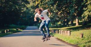 La acción tiró de un skater que patinaba, haciendo trucos y el salto Fotos de archivo