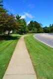 La acera local de la ciudad sigue junto al camino foto de archivo