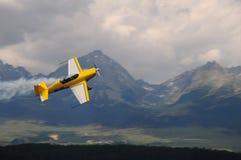 La acrobacia aérea en las montañas - aeroplano del weer fotografía de archivo